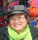 an East Asian women smiling wearing a cap, glasses, and a soft green scarf