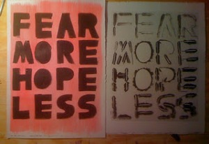 """The image is a photograph of handmade print next to one of the stencils. They read """"FEAR MORE HOPE LESS""""."""